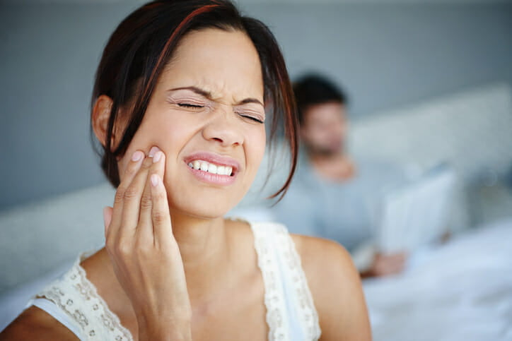Shot of a woman sitting on the side of her bed with bad toothache